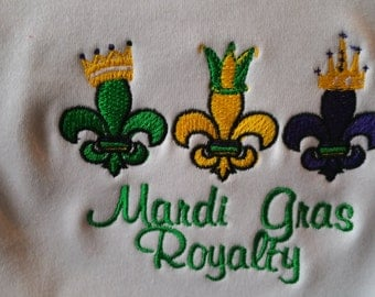 Mardi Gras Royalty White Baby Bib  trimmed in Purple with Purple,Gold, and  Green Fleur De Lis with Mardi Gras Royalty in Purple