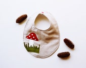 Natural linen baby bib with red toadstool