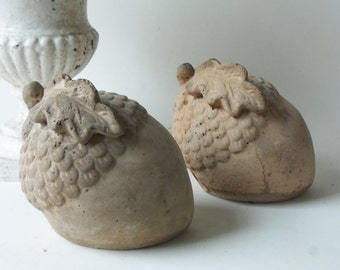 two cement acorns