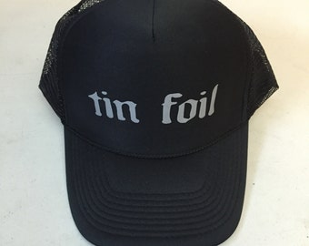 "Trucker Hat with words ""tin foil"" printed on it"
