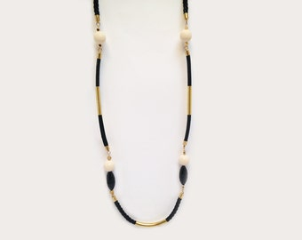 Long black and cream necklace with beads, brass and leather