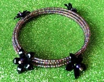 Purple coloured Glass Rocaille Memory Wire Cuff Bracelet with Black Plastic Flowers by JulieDeeleyJewellery on Etsy