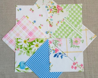 64 5-inch charm squares cut from vintage sheets in pink, blue, & green