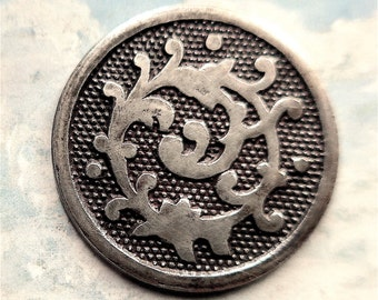 18th. century silver plated button, antique, a scroll design reminiscent of seaweed with a dotted background, plain border, brass
