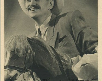 Smling mustached man on toy horse antique photo