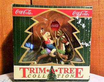 Coca Cola elf riding on a carousel reindeer and holding a bottle of Coke ornament