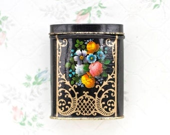Colorful little tin box with Flowers against Balck