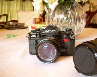 1980 Canon A-1 SLR 35mm film camera with telescope lens and case.