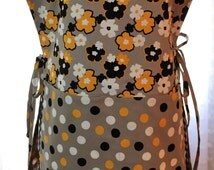 Full coverage cobbler apron - done in a quality taupe cotton with a plethora of gold, black and white flowers and polka dots .