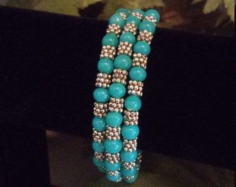 Turquoise glass beads with silver plated spacers on memory wire.