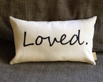 """Natural canvas """"Loved."""" lumbar pillow,  hand painted in black and ideal for dorm, bedroom, or livingroom comfort."""