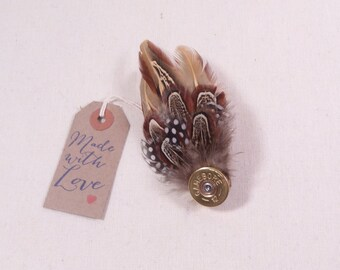 Feather brooch with shotgun cap