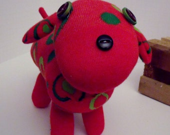 Sock Dog That is Similar to a Dachshund With Short Legs and a Long Body With Button Eyes and Nose Made from a Red Sock with Green Circles