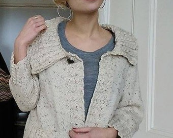 Cream flecked wool cardigan with cable feature to pockets, collar & edging.