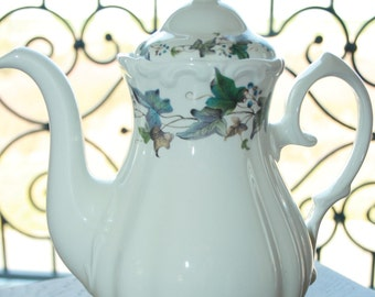 Romantic looking teapot with lovely looking ivy leaves in green colors