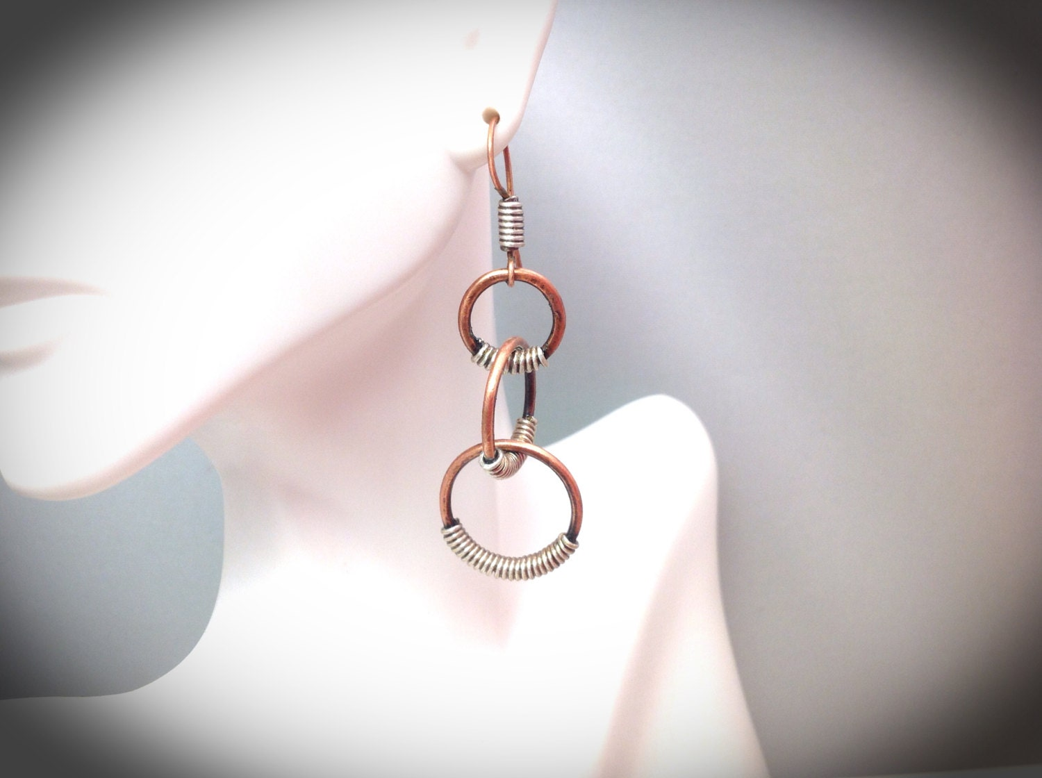 Triple copper and silver coiled wire wrapped hoop earrings.