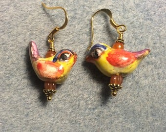 Yellow, orange and purple ceramic songbird earrings adorned with orange Czech glass beads.