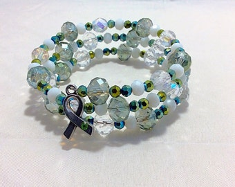 Green memory wire bracelet with charm