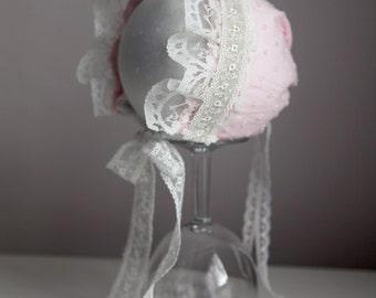 A newborn Pale Pink Baby Bonnet photography prop