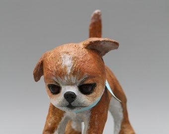 sculpture papier mache of a puppy chihuahua with her Ribbon