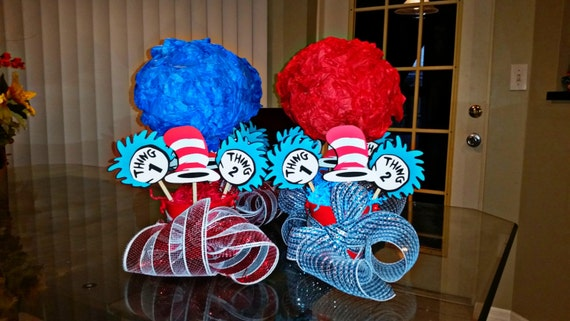 "Two of these tables had centerpieces which I created out of candlesticks which I had spray painted red then attached ""thing 1"" and ""thing 2"" tags onto. I then attached a blue tissue pom onto the top of the candlesticks as these reminded me to the crazy hair of each of the ""Things""."