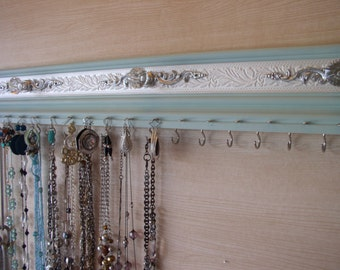 Jewelry organizer for both necklaces and earrings in a light robins egg blue. This wall rack is both functional and pretty, with ------hooks