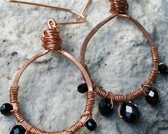 Hand hammered copper hoop earrings with multi faceted black crystal beads and wire wrap.