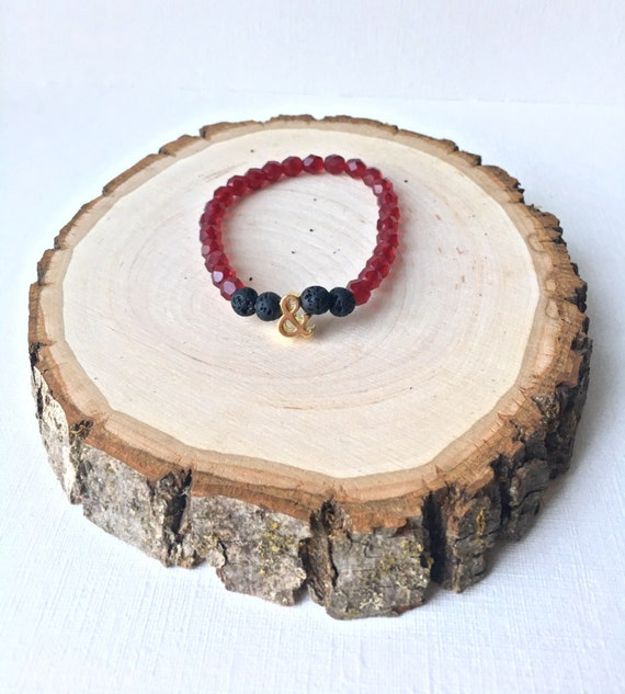 Ampersand Essential Oil Diffuser Bracelet - Gold Ampersand charm with black lava stone and cranberry czech beads stretch bracelet