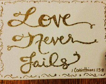 """5x7 White Canvas Frame """"Love Never Fails"""" with Gold or Silver Writing."""