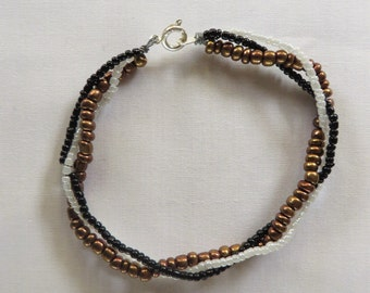 Three strand braided bracelet bronze, black and white coloured