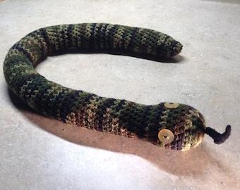 Crocheted stuffed snake in green camouflage