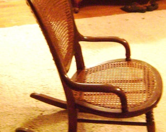 Antique Hand-Carved Walnut Cane Back and Caned Seat  Rocking Chair from the early 1800s in terrific condition.