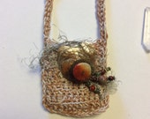 Crocheted medicine pouch necklace with small glass bottle and quartz crystal point
