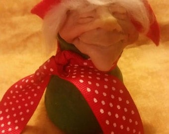 Hand sculpted elf in a holiday bag.