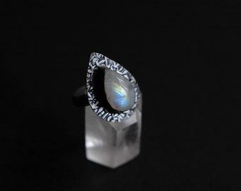 Natural rainbow moonstone oxidized sterling silver ring with drop shaped textured setting. Size 6