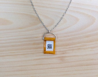 Cat in Japanese calligraphy on a orange minimal necklace