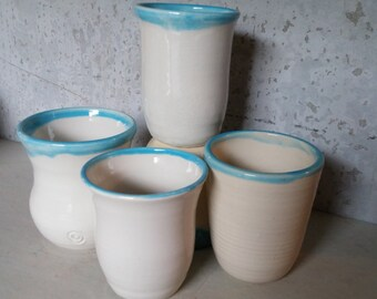White stoneware handthrown cups. Blue rim