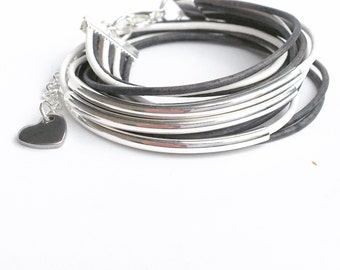 bracelet double wrap in leather white and denim blue wirh silver bangle bracelet accents. lobster clasp with chain and heart drop.