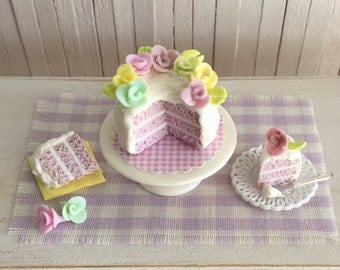 Miniature Couture Cake With Pretty Pastel Roses, A White Cake Stand, And 2 Slices Of Cake