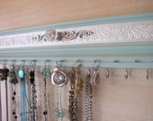 "Jewelry organizer 11 hooks for necklaces, space for 11 pairs of earrings fits in small space 15""long w/ embossed background"