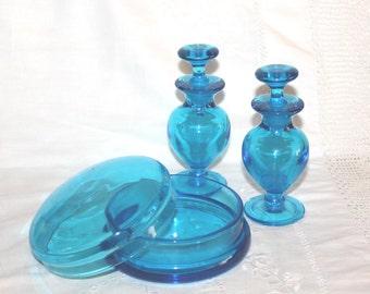 Vibrant turquoise glass perfume bottles and vanity powder bowl