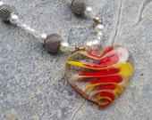 Necklace and Earring Set : Beautiful blown glass heart with a swirl of red, yellow and white with pearls and metal mesh spheres