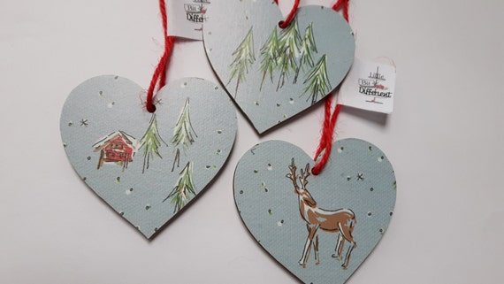 Christmas hanging heart featuring traditional snow covered cabins, reindeers and Chrismtas tree. 6.5cm