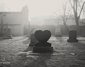 Artistic photography in black and white of a statue of a tombstone-shaped heart, cemetery, sunlight that pierces the mist, foggy morning