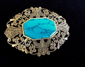 Silver brooch with turquoise center