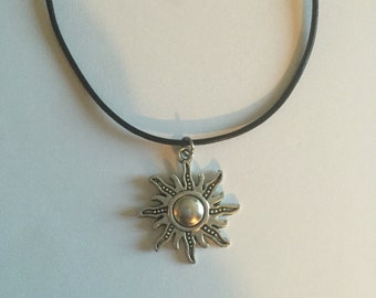 Silver Sun on black leather cord
