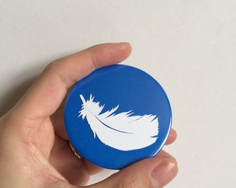 Handcut feather papercut sealed in a pocket mirror