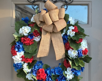 Patriotic red white and blue geranium and hydrangea wreath with burlap bow