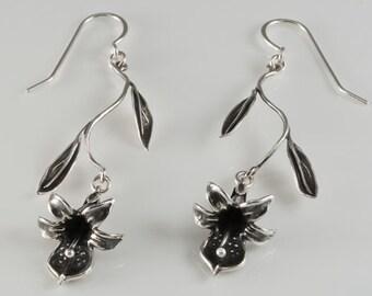 Delicate Black Orchid Earrings Dangle from Leafy Stems