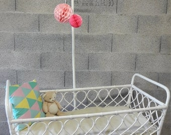 The baby bed in white cane pole with wheels